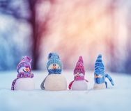 Little snowmans on soft snow on blue background stock photography