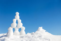 Little snowmen figures building a pyramide in the snow. Concept teamwork and success Stock Image
