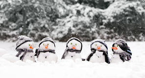 Little snowmen in a group. Carol singing in the snow Royalty Free Stock Images