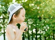 Little and soap bubbles. Little boy blowing soap bubbles Stock Image