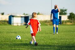 Soccer training for children. Little soccer boy in red and trainer in blue soccer dress are playing soccer on playing field, soccer training for children concept stock image