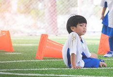 Little soccer boy sitting in soccer field Royalty Free Stock Images