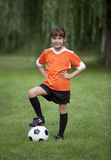 Little Soccer Girl. Full length photo of young girl standing with foot on soccer ball Royalty Free Stock Photo