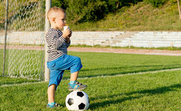Little soccer player drinking juice Royalty Free Stock Photos