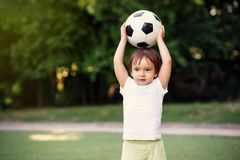 Little soccer player at football field outdoors: toddler boy holding ball above head ready to throw it in sunny day. Summer stock photography