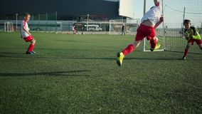 Little soccer player is scoring goal. Running on football field stock video