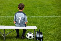 Free Little Soccer Player Sitting On A Wooden Bench And Watching Soccer Game Stock Photo - 117639270
