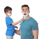 Little son applying shaving foam onto dad`s face stock photography