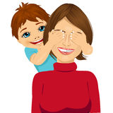 Little son covering her happy mother eyes with his hands smiling Royalty Free Stock Photo