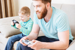 Little son and dad playing computer games at home together. Cheerful little son and dad playing computer games at home together and smiling Stock Image