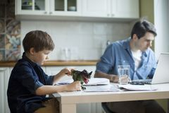 Little son disturbing working freelancer father. Father and son working on laptop. businessman working from home and watching child. spending time with kid royalty free stock image
