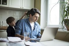 Little son disturbing working freelancer father. Father and son working on laptop. businessman working from home and watching child. spending time with kid royalty free stock photo