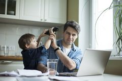Little son disturbing working freelancer father. Father and son working on laptop. businessman working from home and watching child. spending time with kid stock photo