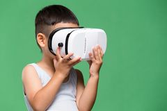 Little son experience though virtual reality device. Asian young little boy royalty free stock photo