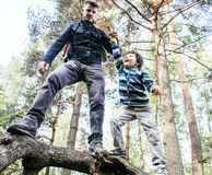 Little son with father climbing on tree together in forest, lifestyle people concept, happy smiling family on summer Stock Images