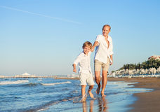Little son and father runs together on sea surfline Stock Photo