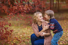 Little son funny scares his mother in park in the autumn Stock Image