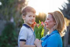 Little son gives bouquet of tulips to mom at Mother`s day. In sunset Stock Photo