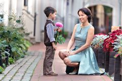 Little son giving a flower to mother. Little boy giving flower to his mom on mother's day Stock Image