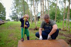 Little son helping his father with building work.  Stock Photo