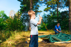 Little son helps to establish a tent Royalty Free Stock Photos