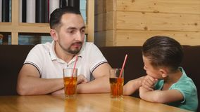 Little son and her father dining at cafe.  stock footage