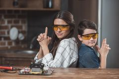 Little son and his beautiful mother wearing protective glasses posing and making gesture as if holding. Pistols stock images