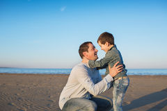 Little son and his father sit and look each other on a beach Royalty Free Stock Photo