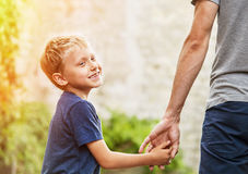 Little son hold his father for hand Stock Photos