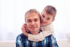 Little son hugging the head of his father. Close-up of joyful father and son. Heartwarming hugs. Little son hugs his father on head. The moment of relaxation and Royalty Free Stock Photo