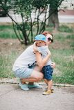 Little son hugging his mother. Fashion little boy hugging his mother Stock Images