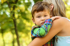 Little son hugging his mother. Loving little son hugging his mother in summer park Stock Images