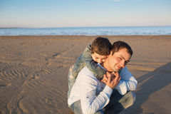 Little son hugs his father on a beach Stock Image