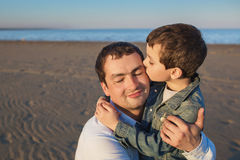 Little son kisses his father on a beach Royalty Free Stock Photo