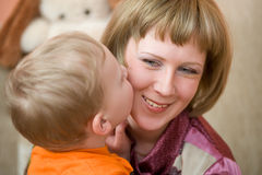 Little son kisses his Mom Stock Images