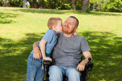 Little son kissing his disabled father. Royalty Free Stock Images