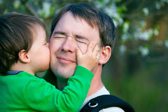 Little son kissing his father outdoors. In spring park Stock Image