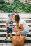 Little son kissing his mother. Fashion little boy kissing his mother Stock Image