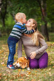 Little son kissing his pregnant mother. Happy family on walk in autumn park stock images