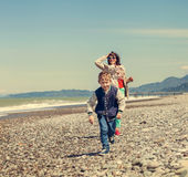 Little son with mother runs together at the sea coast Royalty Free Stock Images