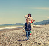 Little son with mother runs together at the sea coast Stock Photos