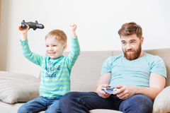 Little son playing computer games with father and winning. Cheerful excited little son playing computer games with father and winning Stock Photography