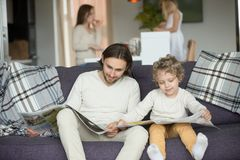 Little son pretending reading newspaper sitting on couch with fa. Ther, cute funny kid imitating dad to be alike spending weekend with family, child boy learning royalty free stock photo