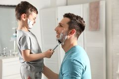 Little son shaving his dad royalty free stock image