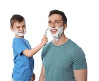 Little son shaving his dad on white royalty free stock photo