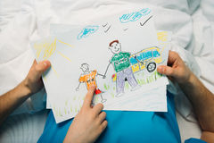 Little son showing sick father his drawings at ward. Dad and son royalty free stock image