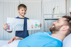 Little son showing sick father his drawings at ward. Dad and son royalty free stock images