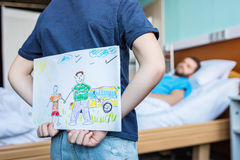 Little son showing sick father his drawings at ward. Dad and son stock image