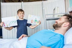 Little son showing sick father his drawings at ward. Dad and son royalty free stock photo