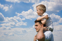 Little son sits on father`s shoulders. Outdoors royalty free stock image